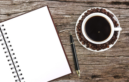dark coffee with notebook & pen on ancient wooden table background photo