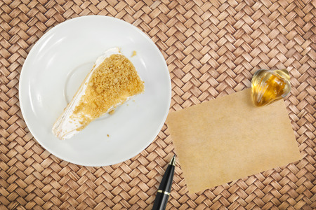 peanut meal cake with paper for note and pen on rattan table background