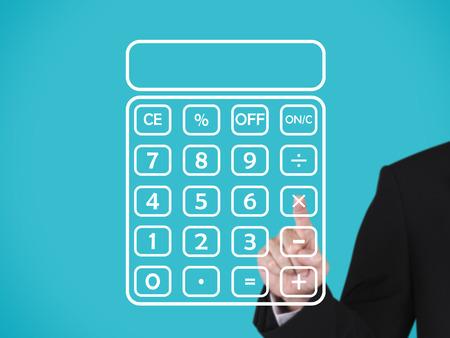 businessman press on blank calculator, blue background Stock Photo