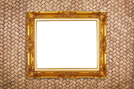 chic gold picture frame on rattan wall background, isolated