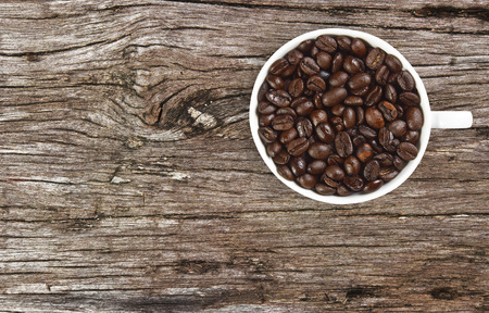 dry beans coffee in white cup on ancient wooden table background