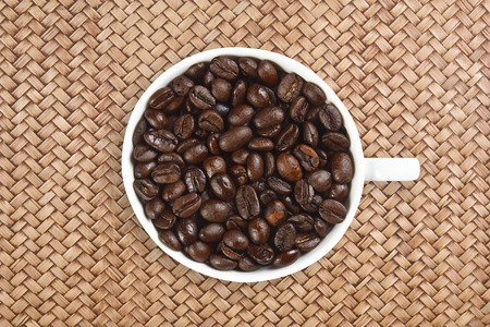 dry beans coffee in white cup on rattan table background Stock Photo