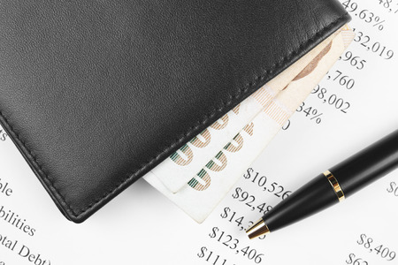investment analysis chart with black wallet, pen and money
