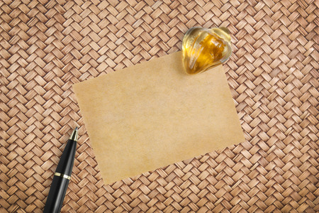 recycle paper for note with paperweight and pen on rattan table background Stock Photo