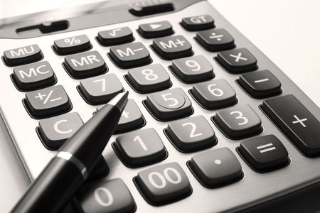 close up calculator with pen on white paper, sepia tone