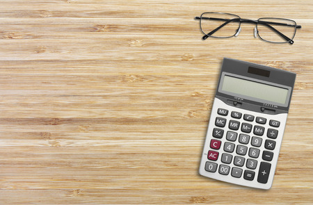 wood texture with calculator and eyeglasses for background, horizontal