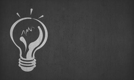 hand drawing light bulb on left side blackboard or chalkboard for your ideas
