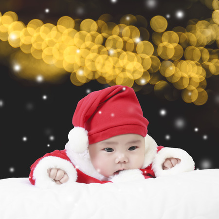 cheerful child wearing santa claus suit and interested snow in the winter for christmas or happy new year on gold bokeh background Stock Photo