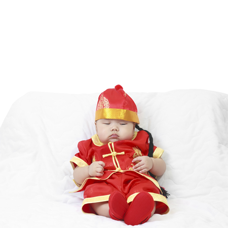 Asian baby boy wearing red Chinese suit or clothes with hat sit and sleeping lay drooling on white bed or sofa for Chinese New Year festiva in studio with copy space Stock Photo
