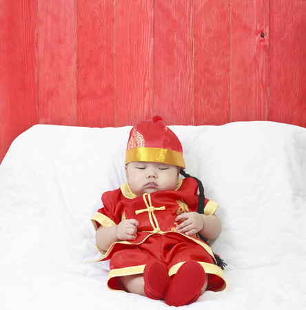 Asian baby boy wearing red Chinese suit or clothes with hat sit and sleeping lay drooling on white bed or sofa and red China wood vintage wall background for Chinese New Year festiva with copy space