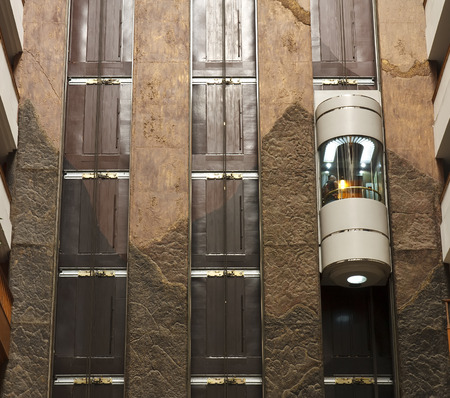 glass capsule elevator with people or tourist in the lift on vintage wall in the hall at luxury hotel or building Stock Photo
