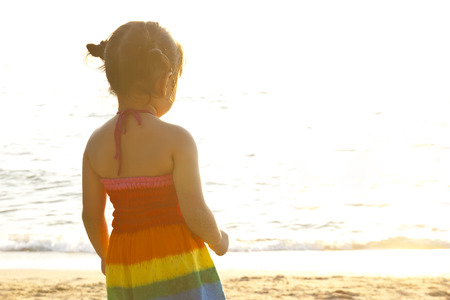abstract cute baby girl wearing rainbow fashion clothes standing on the sea or beach with sunlight and missing someone or lonely in the dream for scene or background