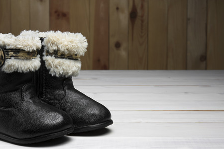 old or secondhand black fur and ribbon boots shoes with leather for children or kids foot for winter or fashion on white vintage wood floor or table with wooden wall and copyspace