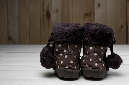 old or secondhand children brown fur boots shoes back side with flannel fabric for winter or foot fashion on vintage white wood floor or table with wooden wall and copyspace Stock Photo