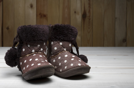 old or secondhand brown fur boots shoes with flannel fabric kids or children for winter or foot fashion on vintage white wood floor or table with wooden wall and copyspace Stock Photo