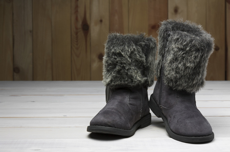 old or secondhand black fur boots shoes with leather kids or children for winter or foot fashion on vintage white wood floor or table with wooden wall and copyspace Stockfoto