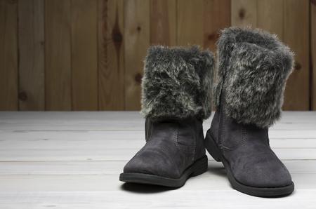 oude of tweedehands zwarte vacht laarzen schoenen met leren kinderen of kinderen voor de winter of de voet mode op vintage witte houten vloer of een tafel met houten wand en copyspace Stockfoto