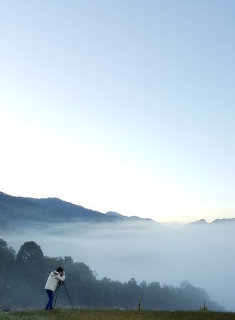 Professional photographer takes landscape photos with camera on tripod on top of mountain for sea of mist or fog at sunrise and soft focus, capture by smartphone
