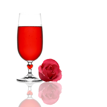 front view red wine chilled in clear glass and heart with red rose petal flower and drop of water for romantic love scene or valentine day on white with reflection shadow, isolated with space Stock Photo