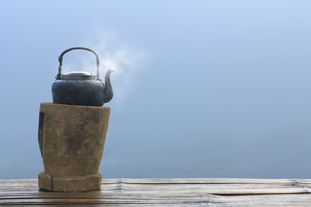 old and black retro kettle for coffee or tea with hot steam or smoke place on wood platform and table or floor in the morning at countryside with sea of mist or fog background and copyspace