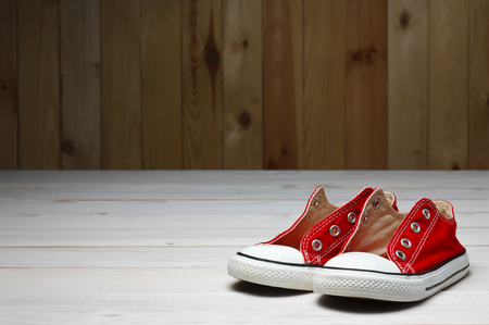 red canvas shoes or sneakers old for kids or baby and child foot on vintage white wood floor or table and wooden wall front view with copyspace