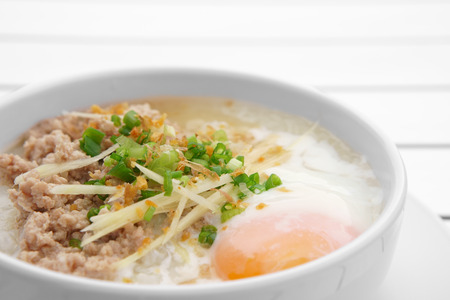 closeup pork chops rice porridge or congee with soft boiled egg and vegetable in the white bowl on the aluminium table for delicious breakfast and clean food in the morning with space Archivio Fotografico