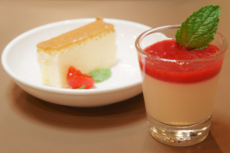 delicious raspberry panna cotta in clear glass and cherry cheese or butter cake on wood table and warm white for sweet dessert or snack at cafe restaurant for breakfast or dinner and background