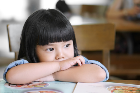Asian children cute or kid girl lonely and sad with tears in the eye on food table because miss mom and dad or parents do not care with thinking something Banco de Imagens