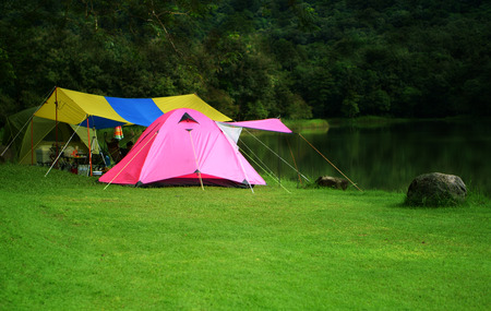 nature landscape pink camping tent under tree and colorful tarp on meadow and stone or rock with lake or river and tree mountain jungle for holiday relax on winter and soft warm sunlight at ched khot