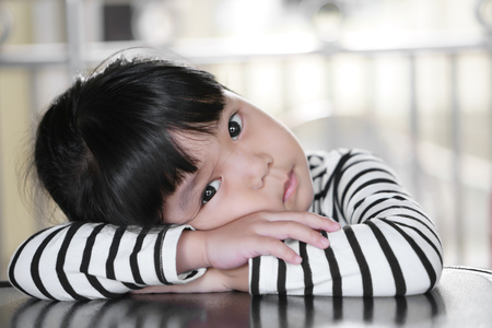Asian children cute or kid girl sleep and open eye for relax on table at nursery or kindergarten