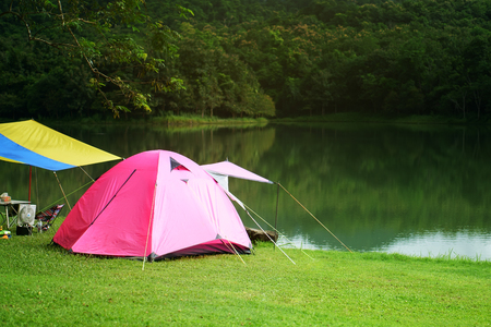 nature landscape pink camping tent under tree and colorful blue with yellow tarp on meadow with lake or river and tree mountain jungle for holiday relax on winter and soft warm sunlight at ched khot Stock Photo