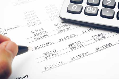 business financial chart analysis or investment benefit with calculator and pen in the hand on paper work and report at office