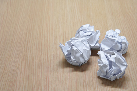 crumpled paper ball for trash of fail idea concept on wood table or floor at working office for background with space Stock Photo