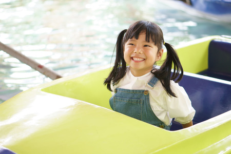 Asian children cute or kid girl enjoy smile and happy fun with boat ride on water or pool in amusement park on summer holiday relax and family vacation Stock Photo