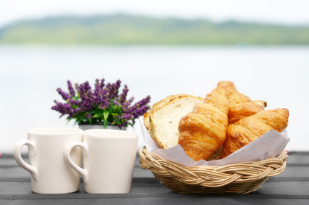 Croissant and cereal bread in wood basket for breakfast in the morning or dessert with two coffee in white cup and flower on black table and lake with nature mountain