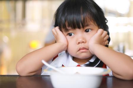 Asiatische Kinder niedlich oder Kind Mädchen Student Magersucht oder traurig mit frei und Stütze oder Hand auf Wange auf Essen Tisch zum Frühstück vor dem Schulbesuch Standard-Bild