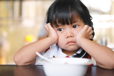 Bambini asiatici carino o ragazzina studentessa anoressia o triste con vacante e puntello o mano a guancia sul tavolo del cibo per colazione prima di andare a scuola per studio Archivio Fotografico