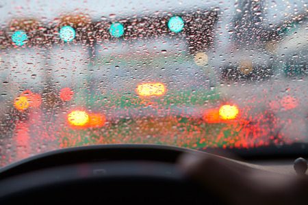 people driving car and water droplet on car mirror or windshield with rain or storm and traffic jam on expressway road although the green light