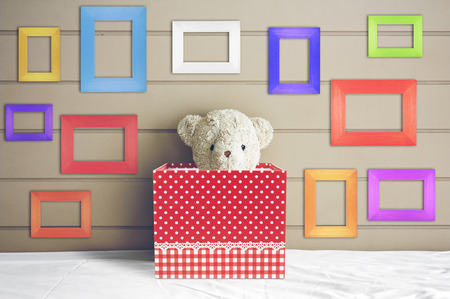 vintage teddy bear doll in red gift box on the white bed with blank multi-color or fancy picture frame at the headboard and brown wall background for gift and surprise on christmas or birthday party