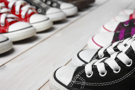 many canvas shoes or sneakers black, red, pink, purple, brown and scott color old for kids or baby foot on vintage white wood floor or table for fashion or background