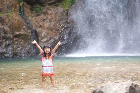 Asian children cute or kid girl smile with fun and enjoy playing water splash on waterfall and holiday relax trip for summer at Jokkradin waterfall
