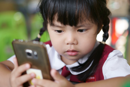 Asian children cute or kid girl student wear school uniform looking smartphone for vdo clip or cartoon and playing the game very concentrate which causes ADHD or Hyperactive Reklamní fotografie - 106603622