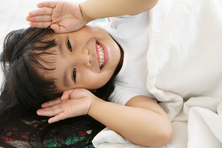 Asian children cute or kid girl sleep with open hand from eye for enjoy playing peekaboo or hide and seek with smile white teeth Banco de Imagens