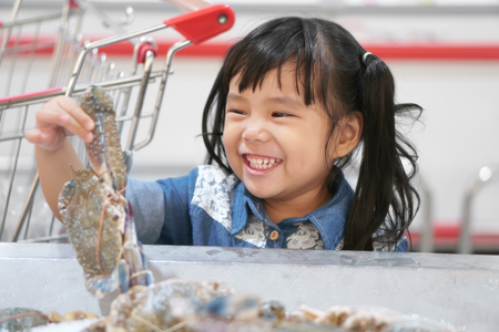 Asian children cute or kid girl holding and choose fresh horse crab in ice tray and fun with smile white teeth for seafood sales or buy and shopping with supermarket cart at supermarket store Stock Photo