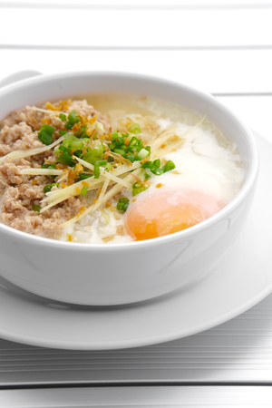 vertical pork chops rice porridge or congee with soft boiled egg and vegetable in the white bowl with spoon on the aluminium table for delicious breakfast and clean food in the morning Stock Photo