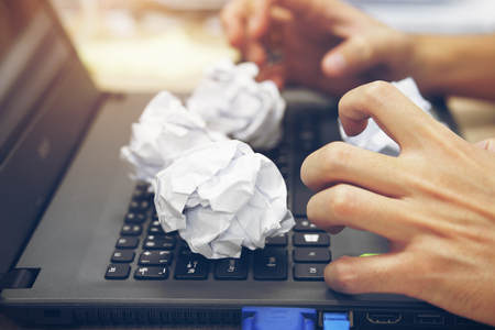 hand of businessman or hacker with strain feeling on computer notebook and crumpled paper ball for trash of fail idea or plan concept on wood table at working office on vintage blue and sunlight Stock Photo