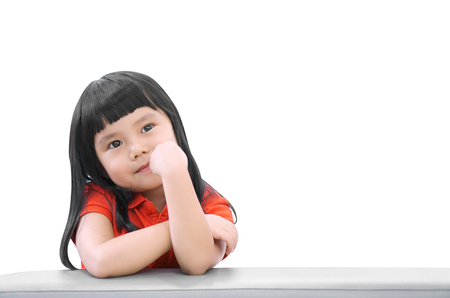 Asian children cute or kid girl think and happy fun or smile with wear red shirt on sofa at preschool or nursery and child hospital on white isolated with space included clipping path