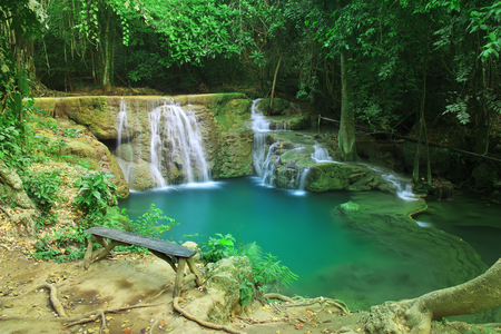 waterfall with relax long wood chair and clear blue and green emerald water with tree and root in the jungle at Huay Mae Khamin waterfall for nature landscape and background Stockfoto