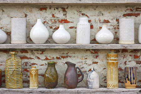 antique white and color vase with jar or flower pot vintage and retro on the old wood shelf and white brick wall for interior or exterior architecture decor