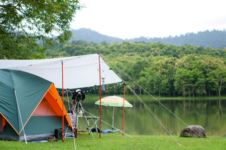 nature orange with green camping tent and gray fly sheet with tent accessory on meadow with lake or river and tree mountain for holiday relax on rainy season and white sky at ched khot Stock Photo